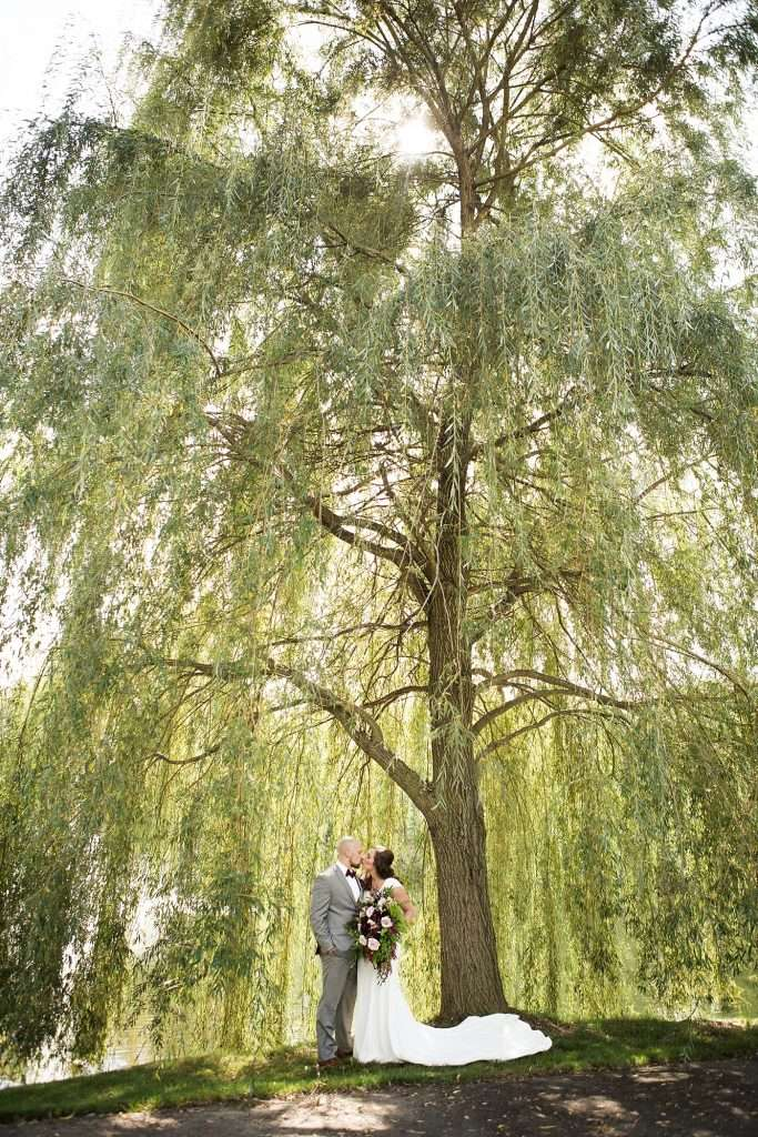 wide angle shot of a bride and groom kissing under a large willow tree