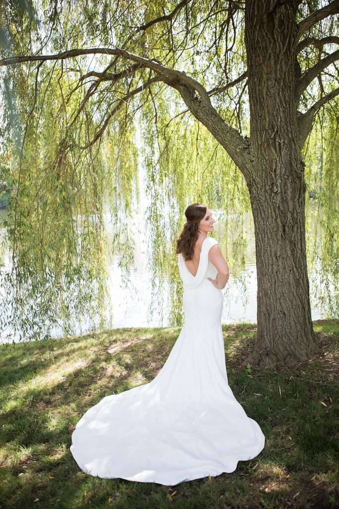 bride wearing a low back wedding gown posing under a large willow tree