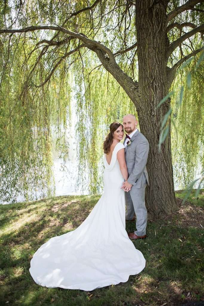 bride wearing a low back wedding gown posing with her groom under a large willow tree