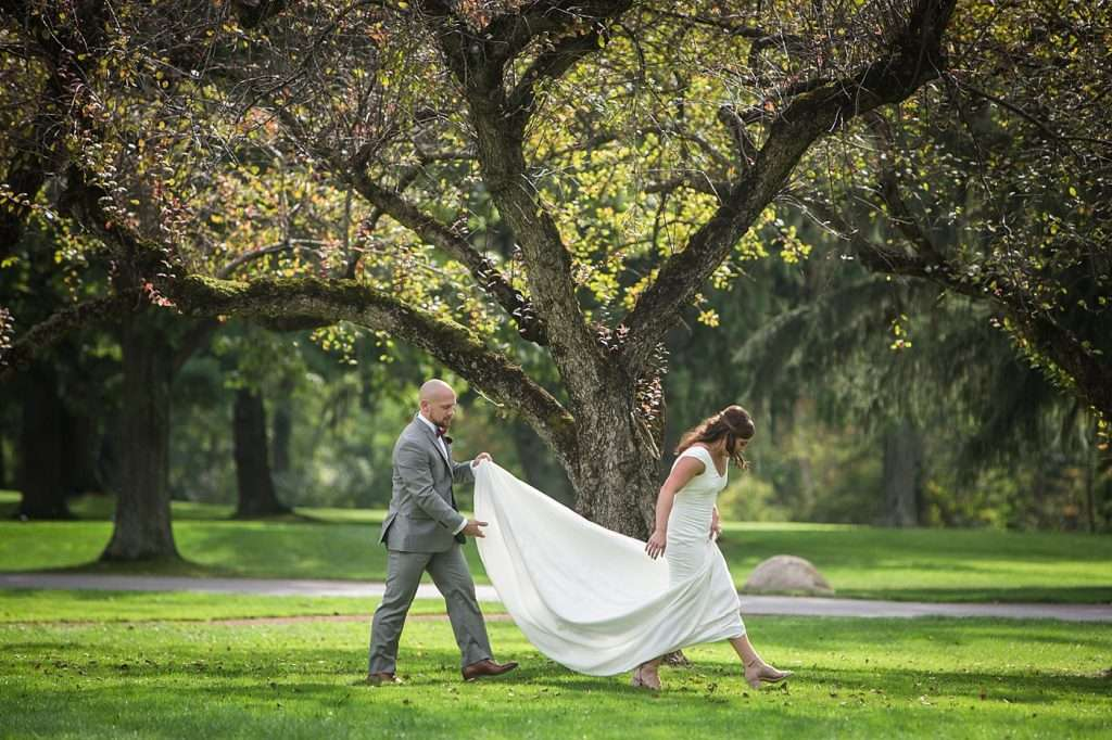candid image of a groom holding his bride's dress as they walk through a field of grass