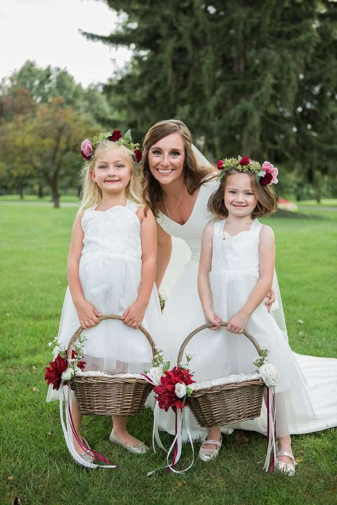 a bride smiles and poses with her two flower girls wearing red and pink flower crowns
