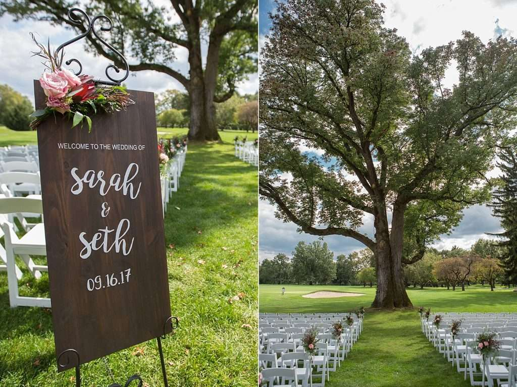 close-up image of a hand painted wooden sign at an outdoor wedding ceremony