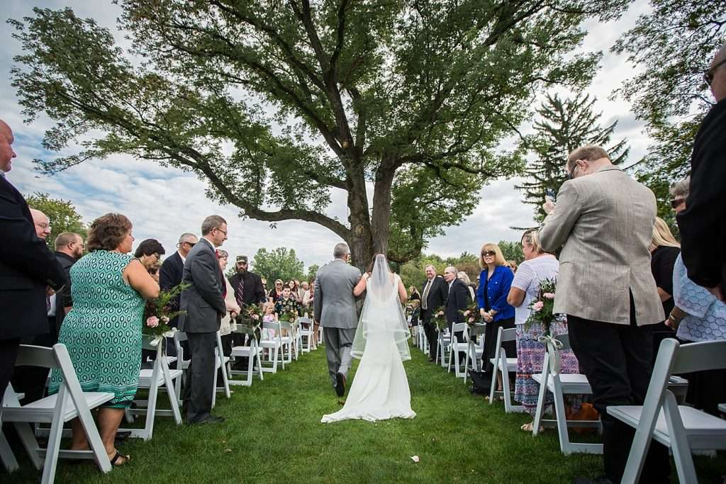 wide angle shot from the back as a bride and her father walk down the aisle during an outdoor wedding ceremony under a large tree