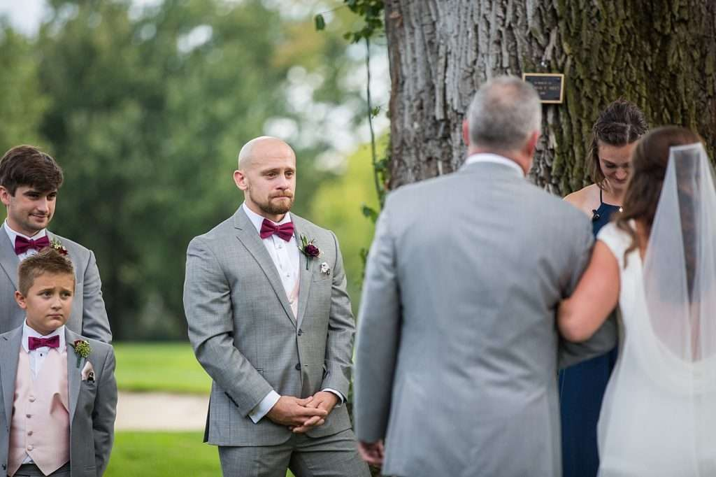 a groom has tears in his eyes as he sees his bride walking down the aisle at their wedding ceremony