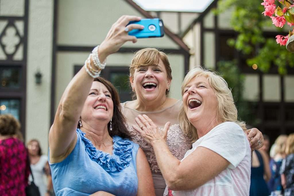 happy wedding guests laugh while taking a selfie