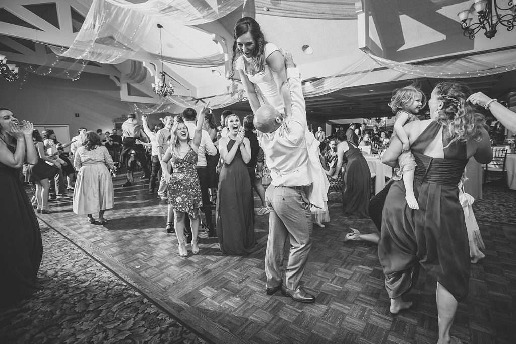 groom lifting up his bride on the dance floor with guests laughing and cheering
