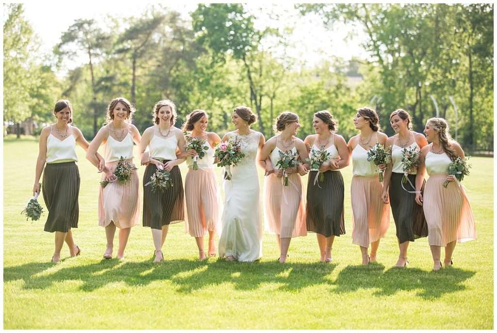 a bride and group of nine smiling and laughing bridesmaids linking arms and walking through the grass