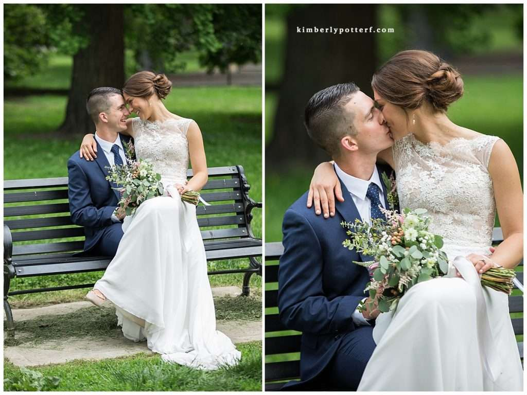 bride and groom sitting on a park bench cuddling