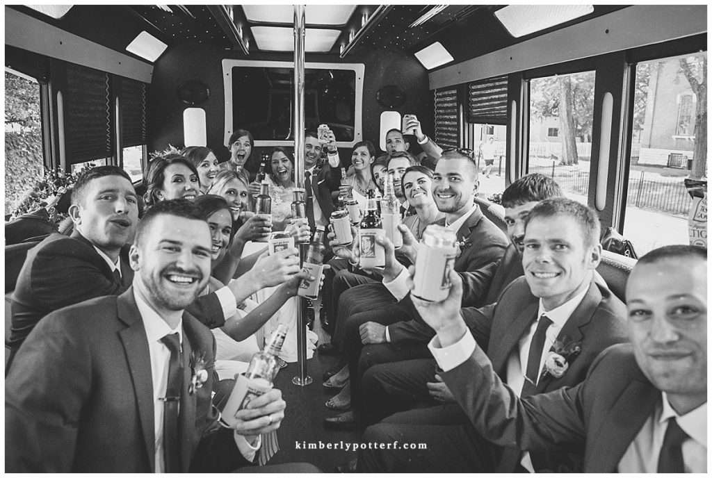 Large bridal party toasting on a party bus
