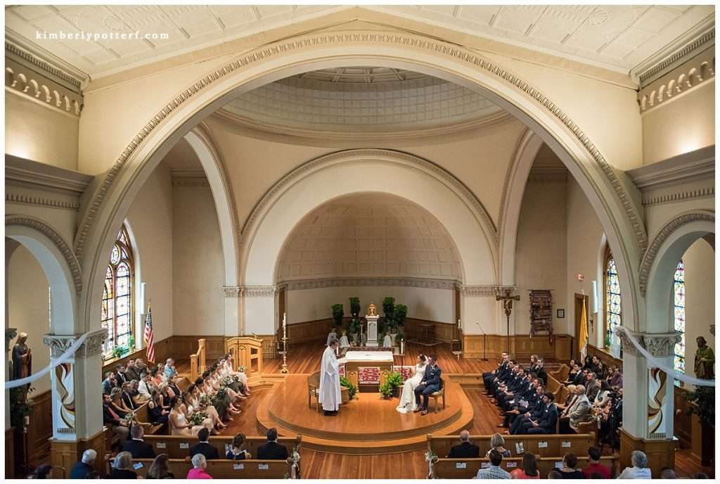 A wide angle view of a wedding ceremony in a Catholic church