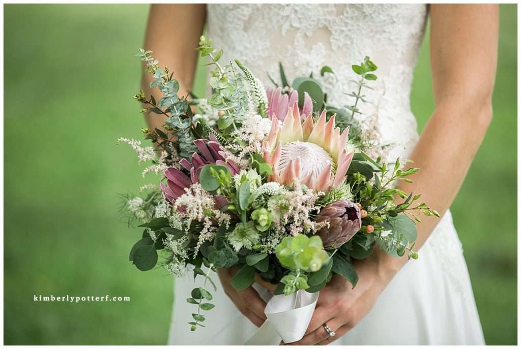 Close-up detailed image of a bride holding a bouquet with proteas