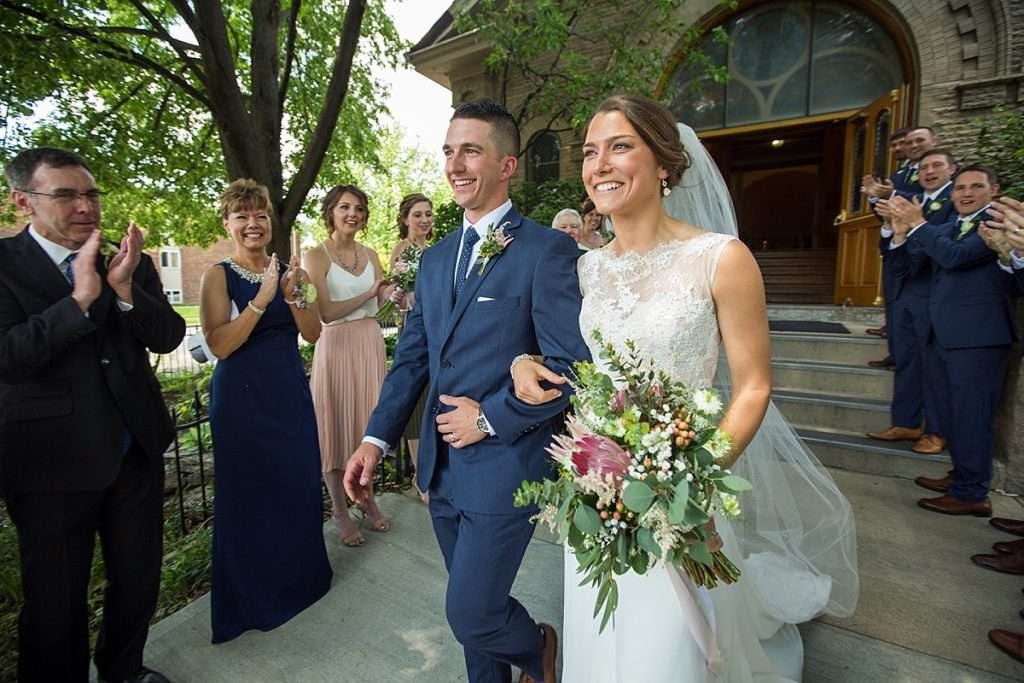 a young bride and groom smiling and walking out of a church