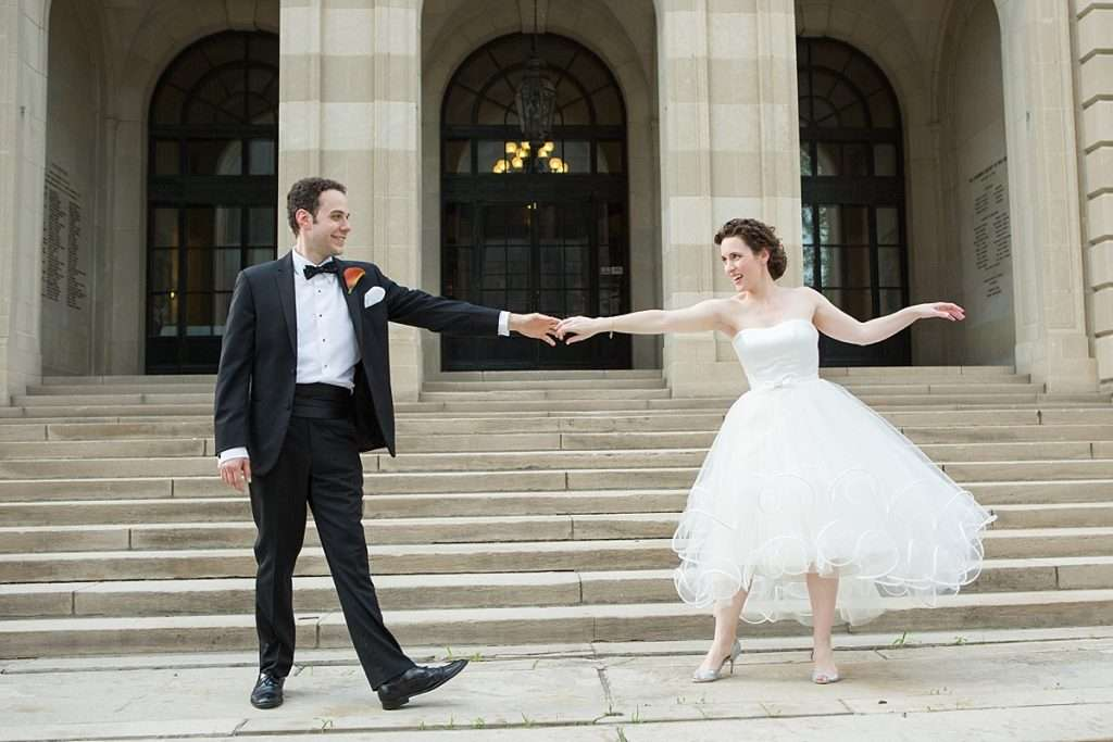 Bride and groom smiling and dancing outside on the steps of the Columbus Museum of Art