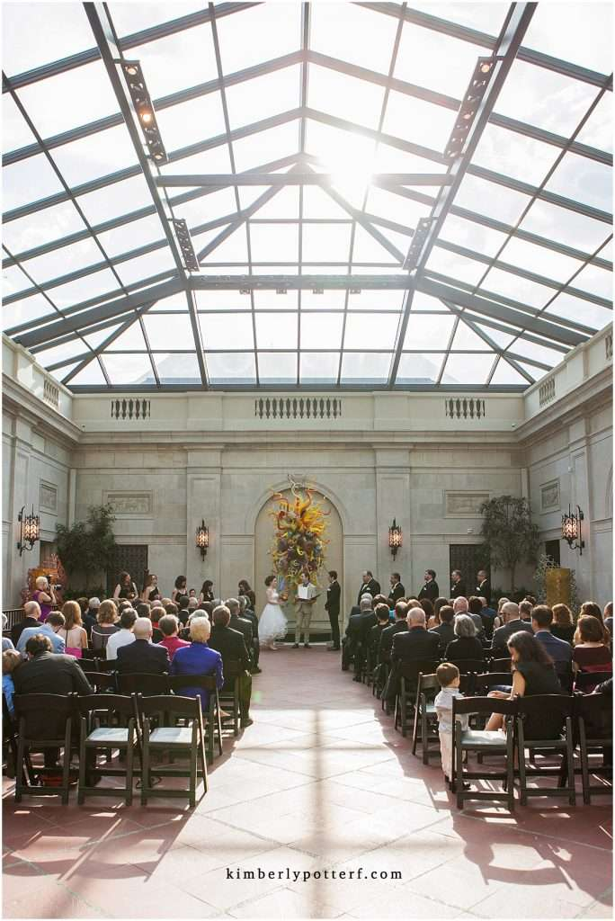 wide angle view of a ceremony at the Columbus Museum of Art. The sun is shining brightly through the glass ceiling.