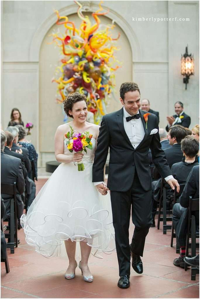 A recently married bride and groom smiling and holding hands as they walk down the aisle of their wedding ceremony.