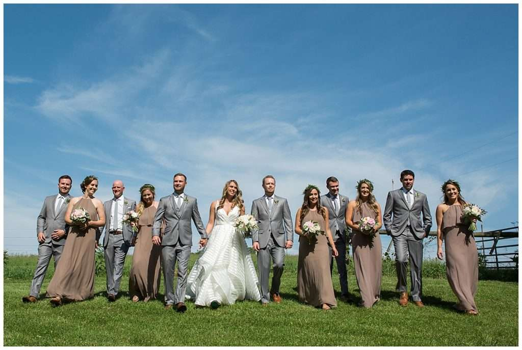 Large bridal party walking down a country hillside on a bright sunny day
