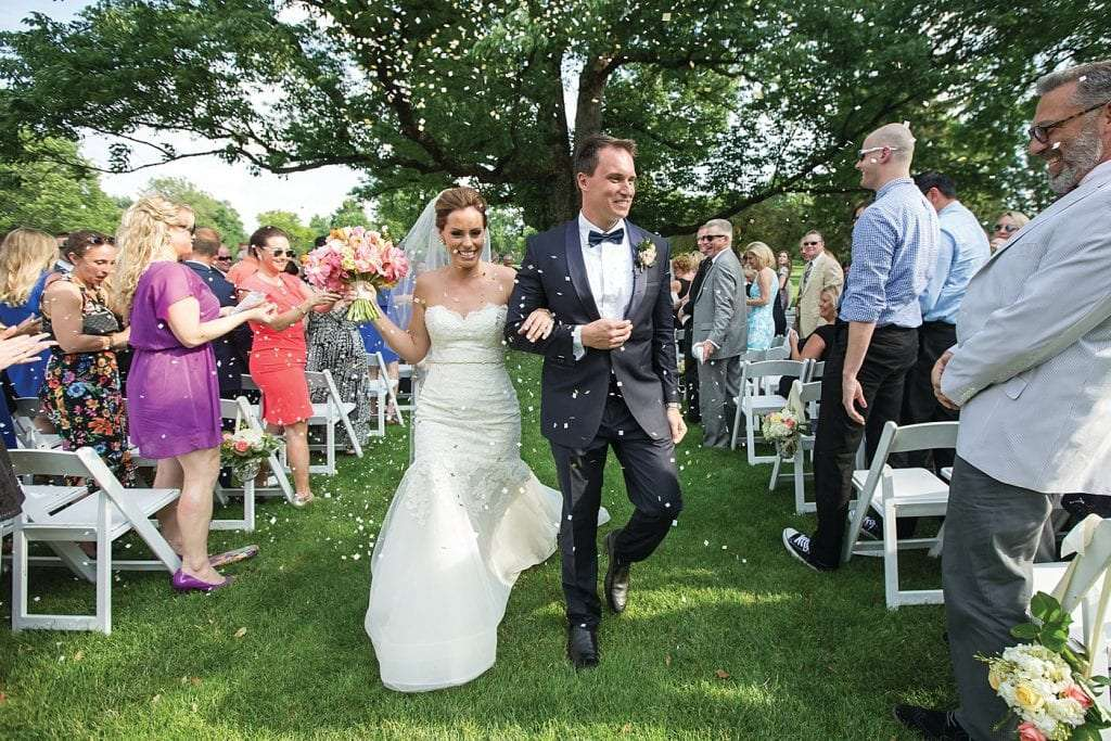 a bride and groom holding hands and smiling as people throw confetti