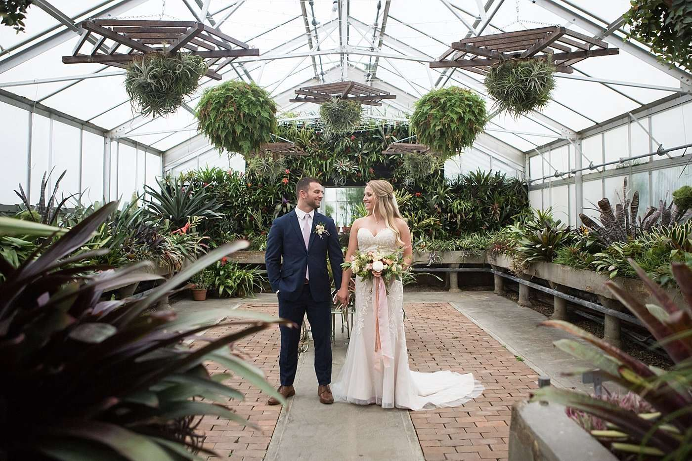 A newly married bride and groom hold hands inside a greenhouse full of lush plants
