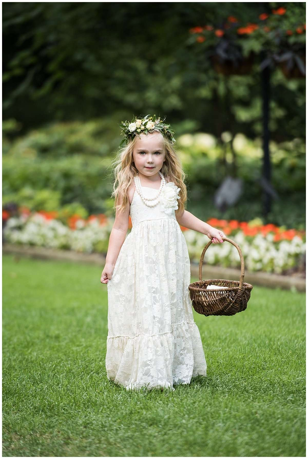 Flowergirl with long blond hair wearing a crown of flowers and holding a basket of petals.