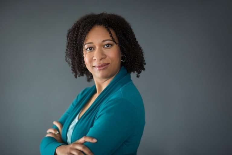 a studio portrait of a black woman in her thirties wearing a blue cardigan looking at the camera with her arms crossed and a soft smile