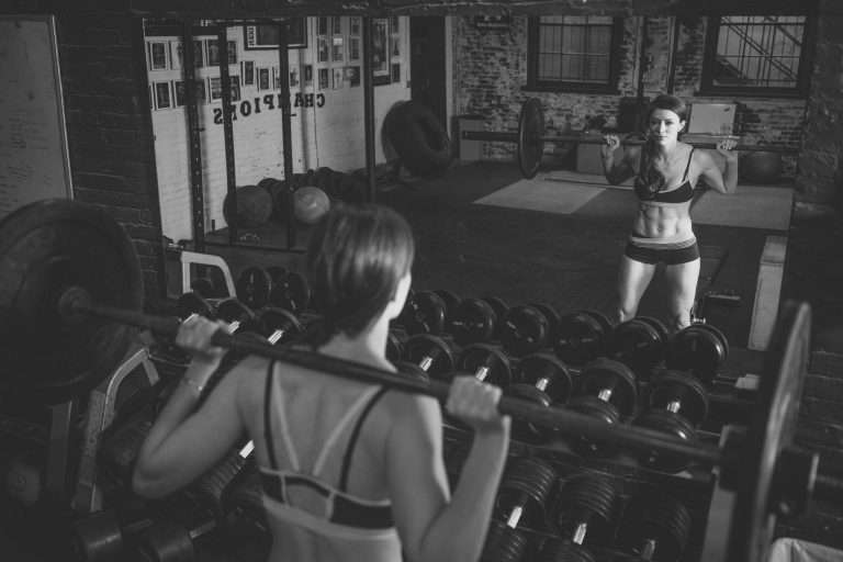 black and white image of a woman holding a barbell