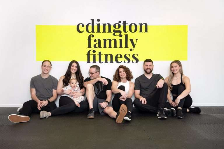 a group of six adults and a baby wearing fitness attire sitting against a wall smiling