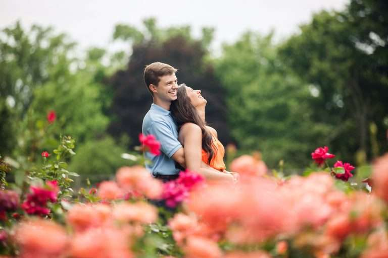 a couple holds each other and laughs in a garden surrounded by orange and red roses