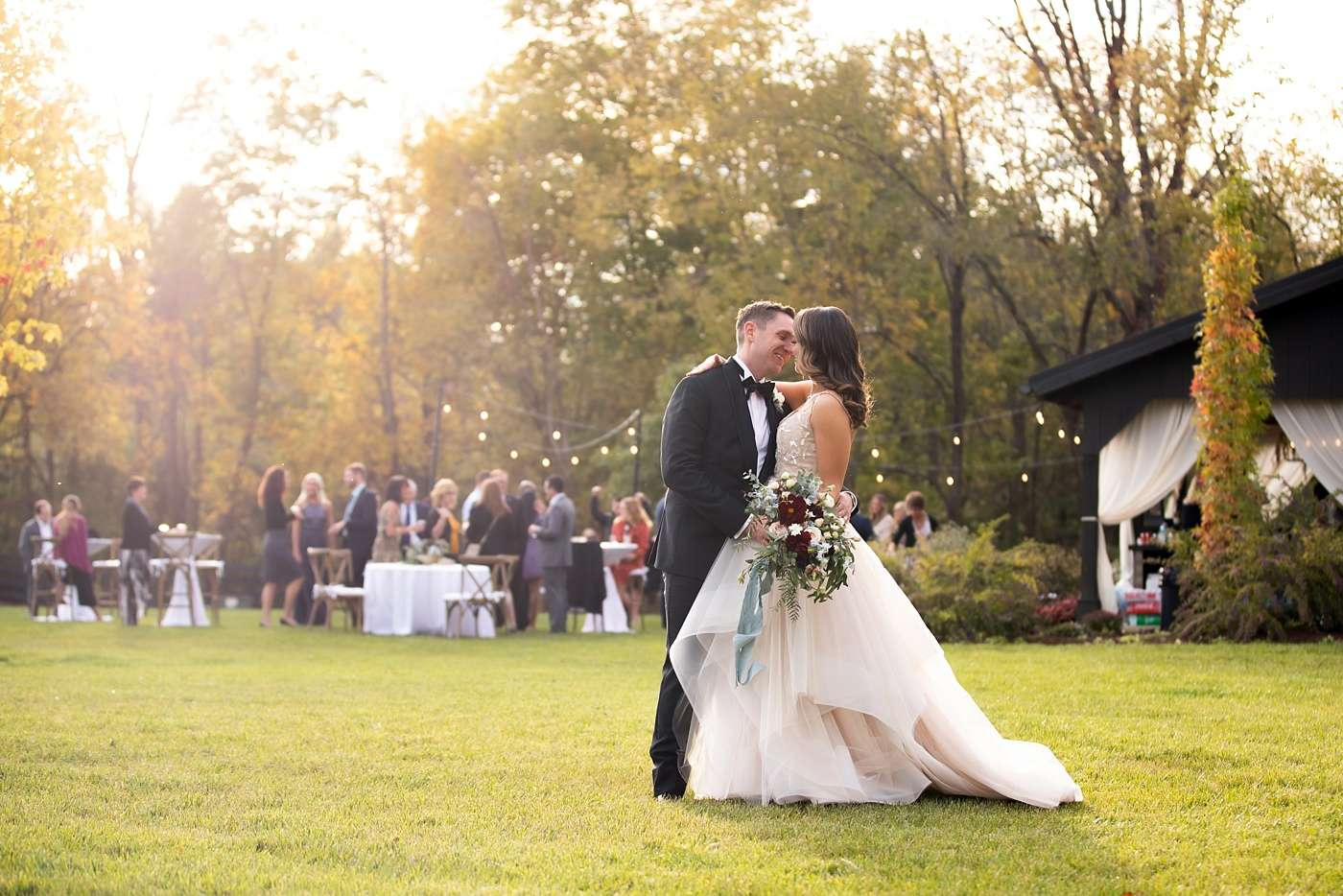 bride and groom looking at each other and smiling against a backdrop of fall foliage at sunset