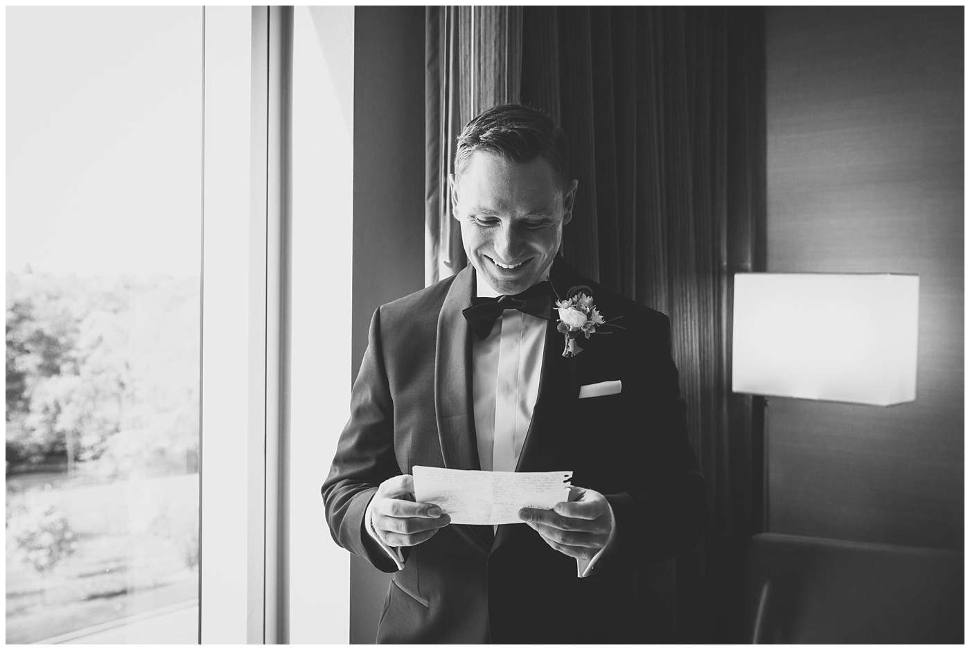 a groom wearing a tuxedo smiling while reading a letter