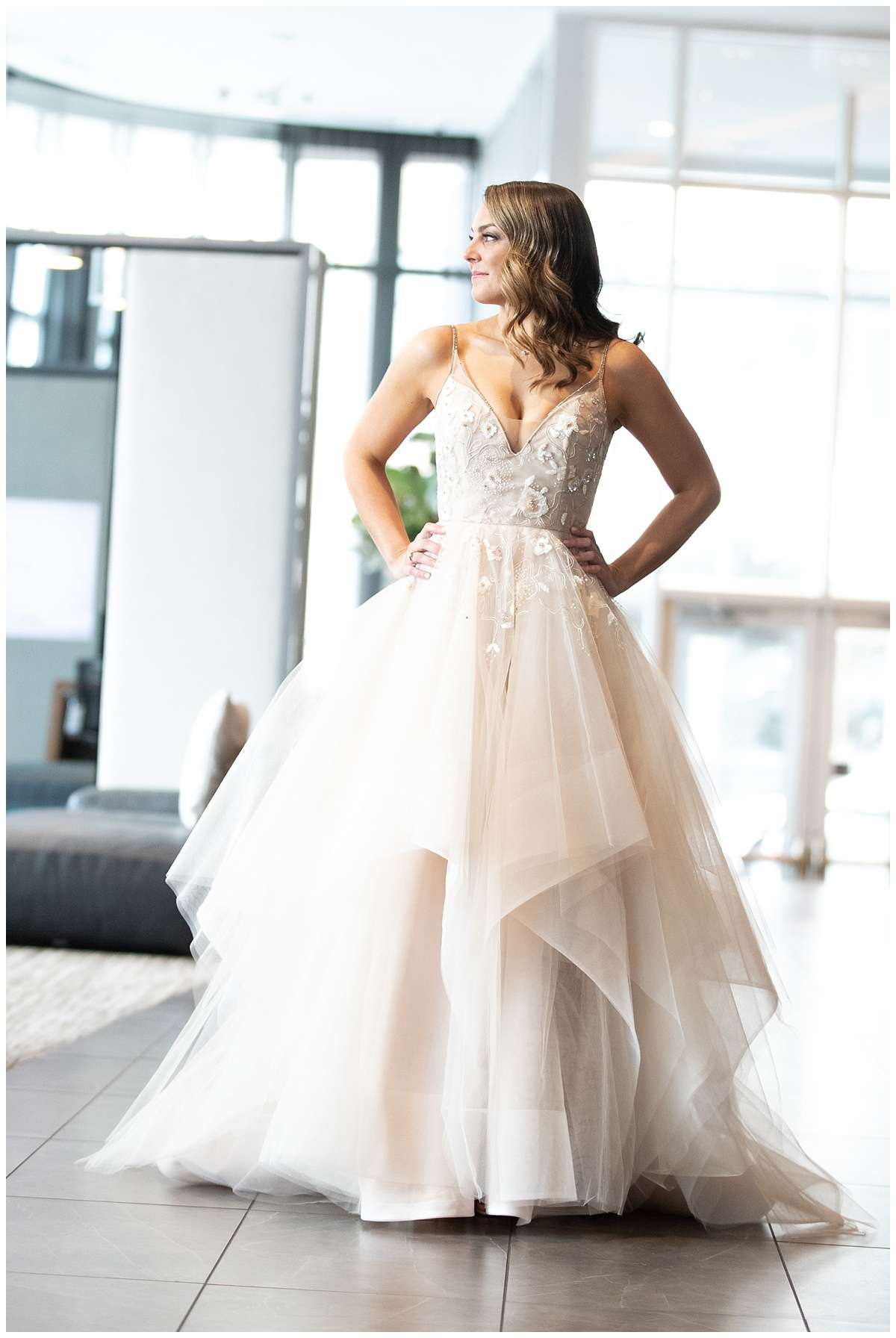a brunette bride wearing a tulle ballgown in a bright space filled with natural light