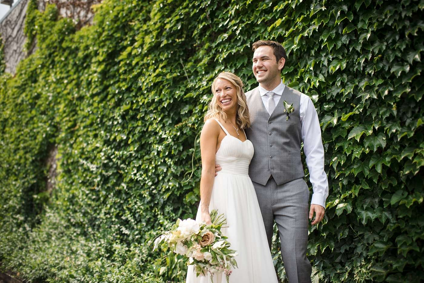 bride and groom standing against a wall of dark green ivy looking back and smiling