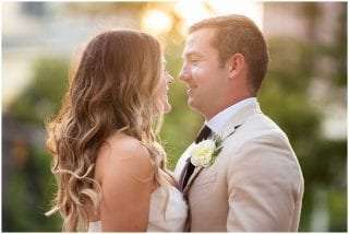a bride and groom smiles at each other with a warm sunset glow behind them