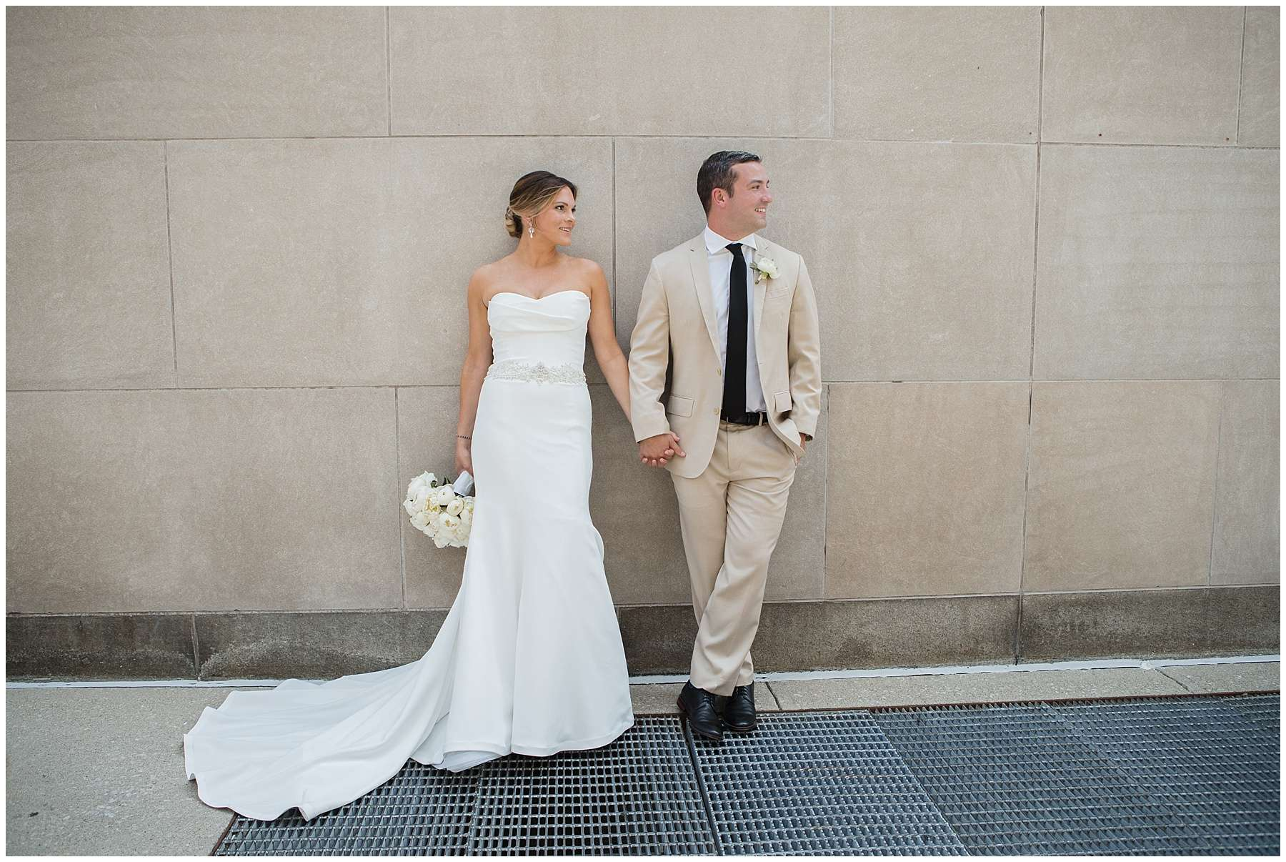 A bride and groom stand side by side along a cement building holding hands and smiling
