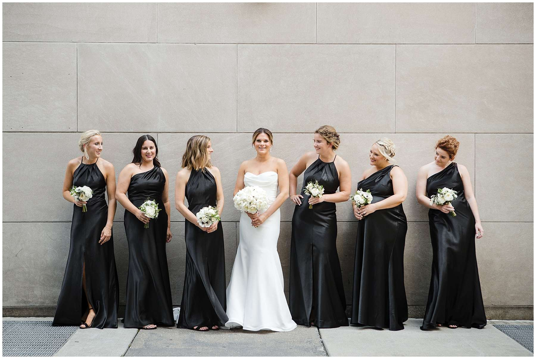 a bride smiles while posing with her bridesmaids who are wearing long black satin dresses and holding small white bouquets