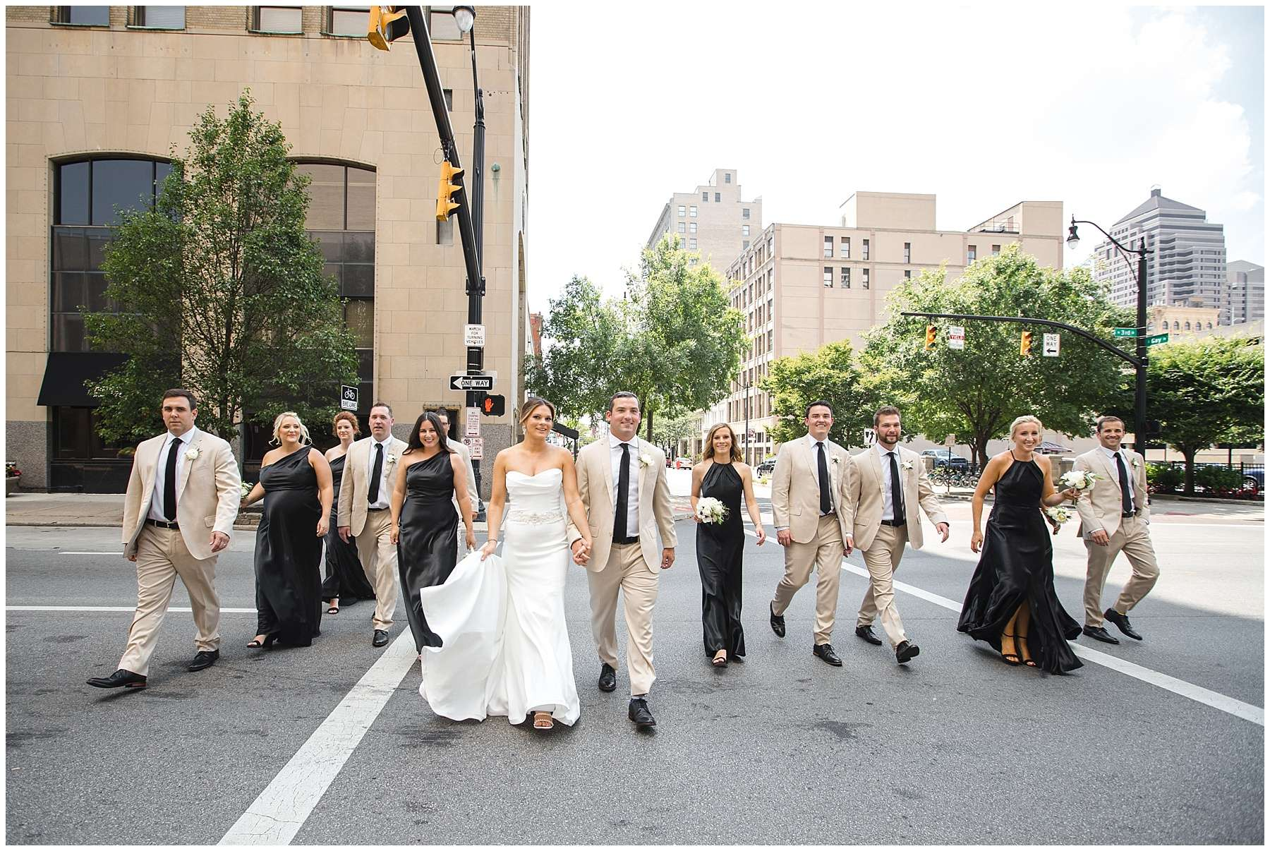 a large group of men and women wearing khaki suits and long black dresses cross a street in a downtown urban area