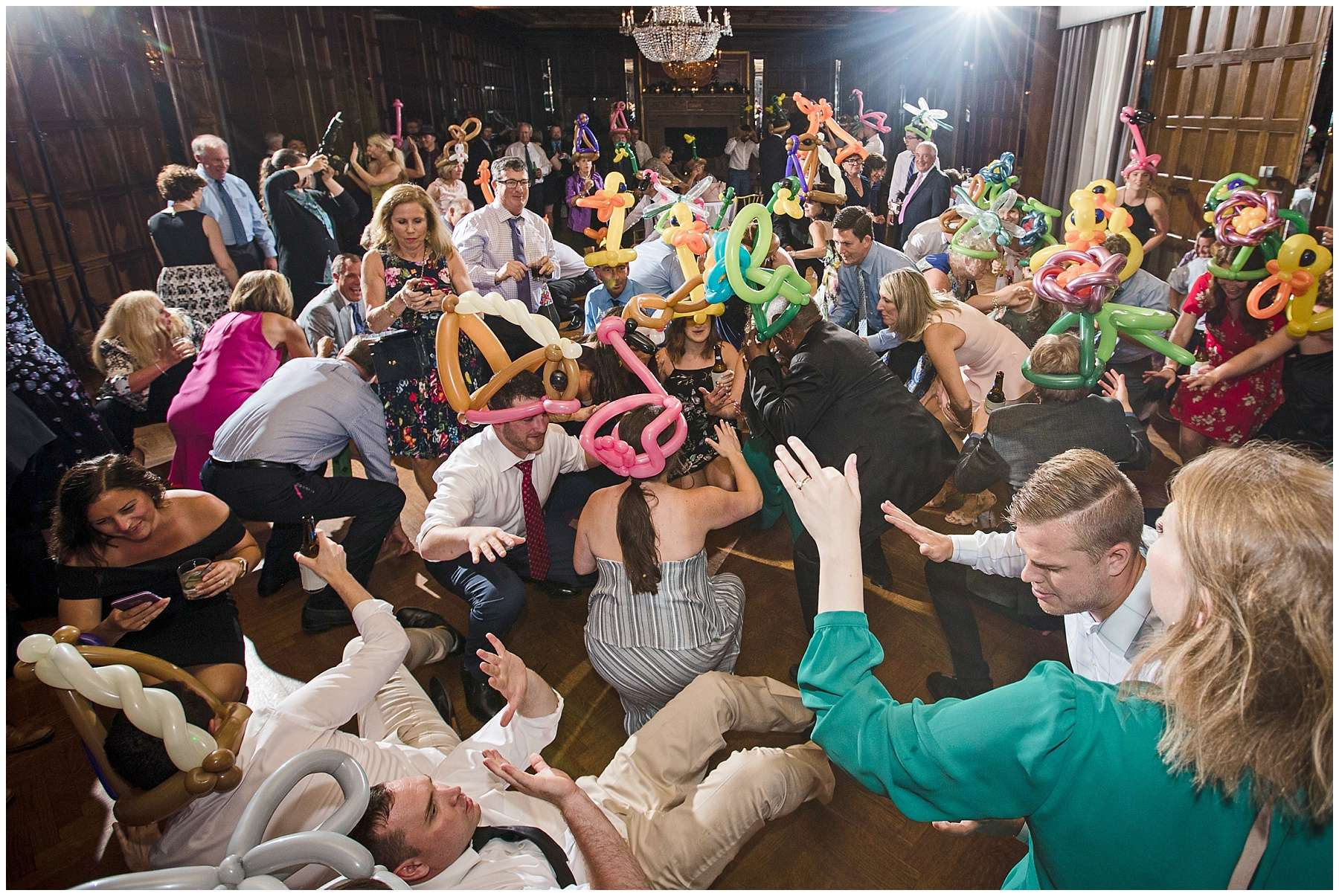 a large group of guests wearing colorful balloon hats dancing at a wedding reception