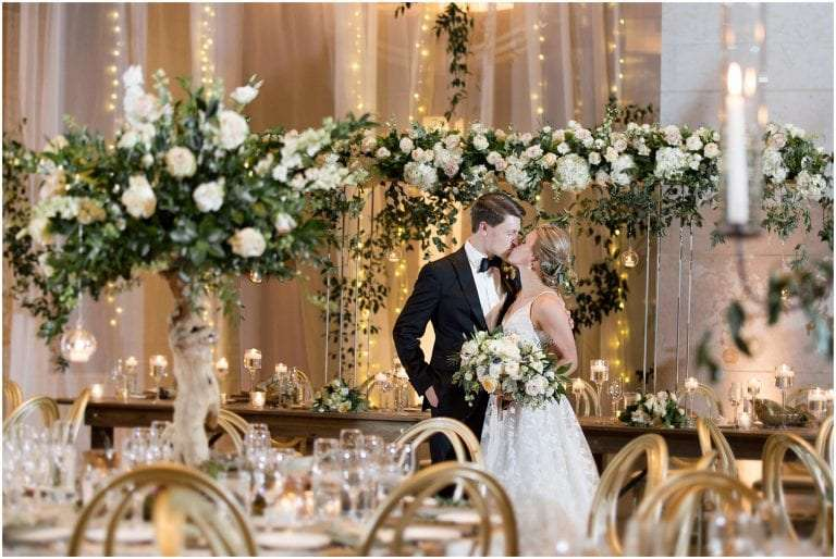 A bride and groom kissing in a ballroom decorated with flowers and candles