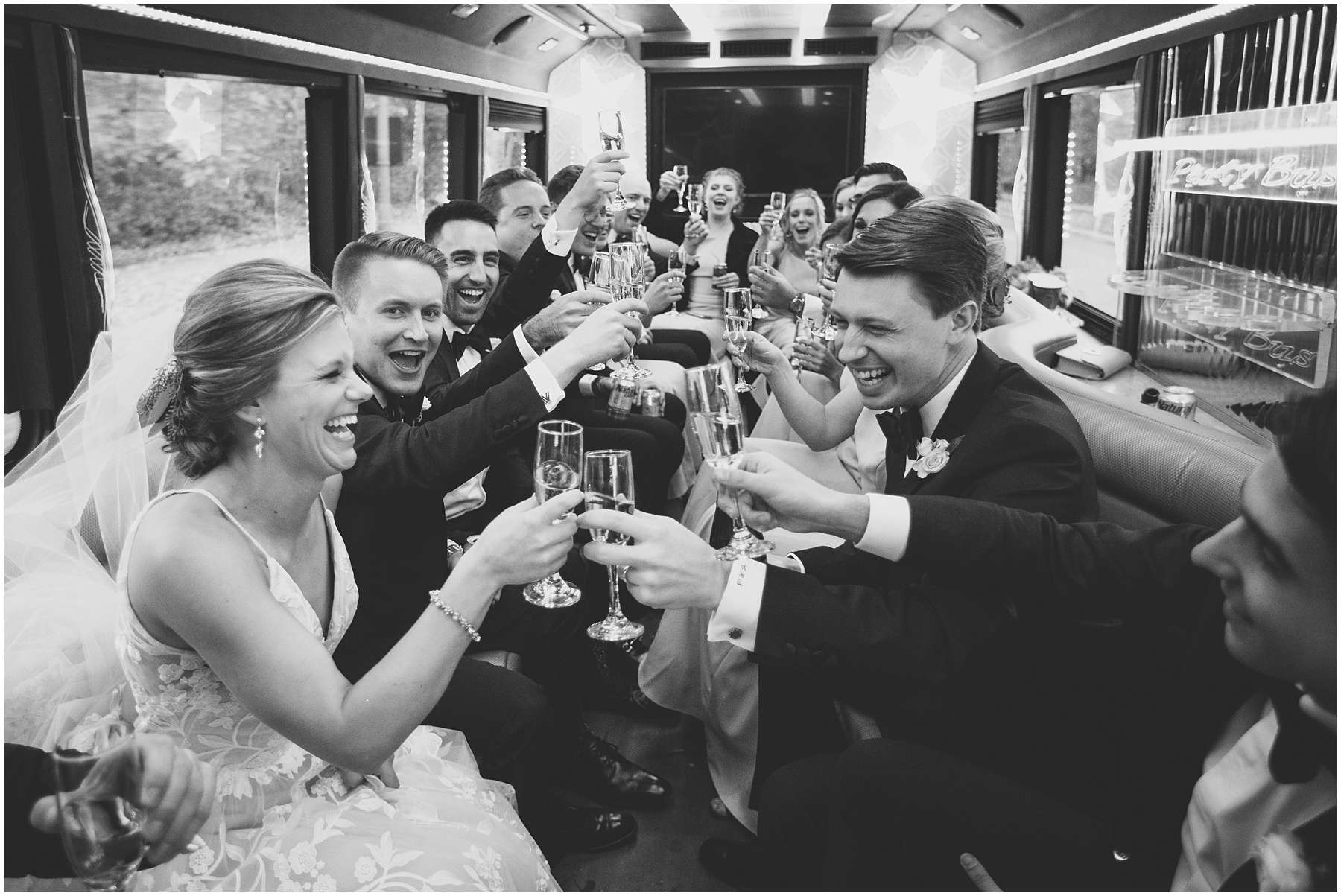black and white photo of a bride and groom sharing a champagne toast and laughing with their bridal party inside a limousine