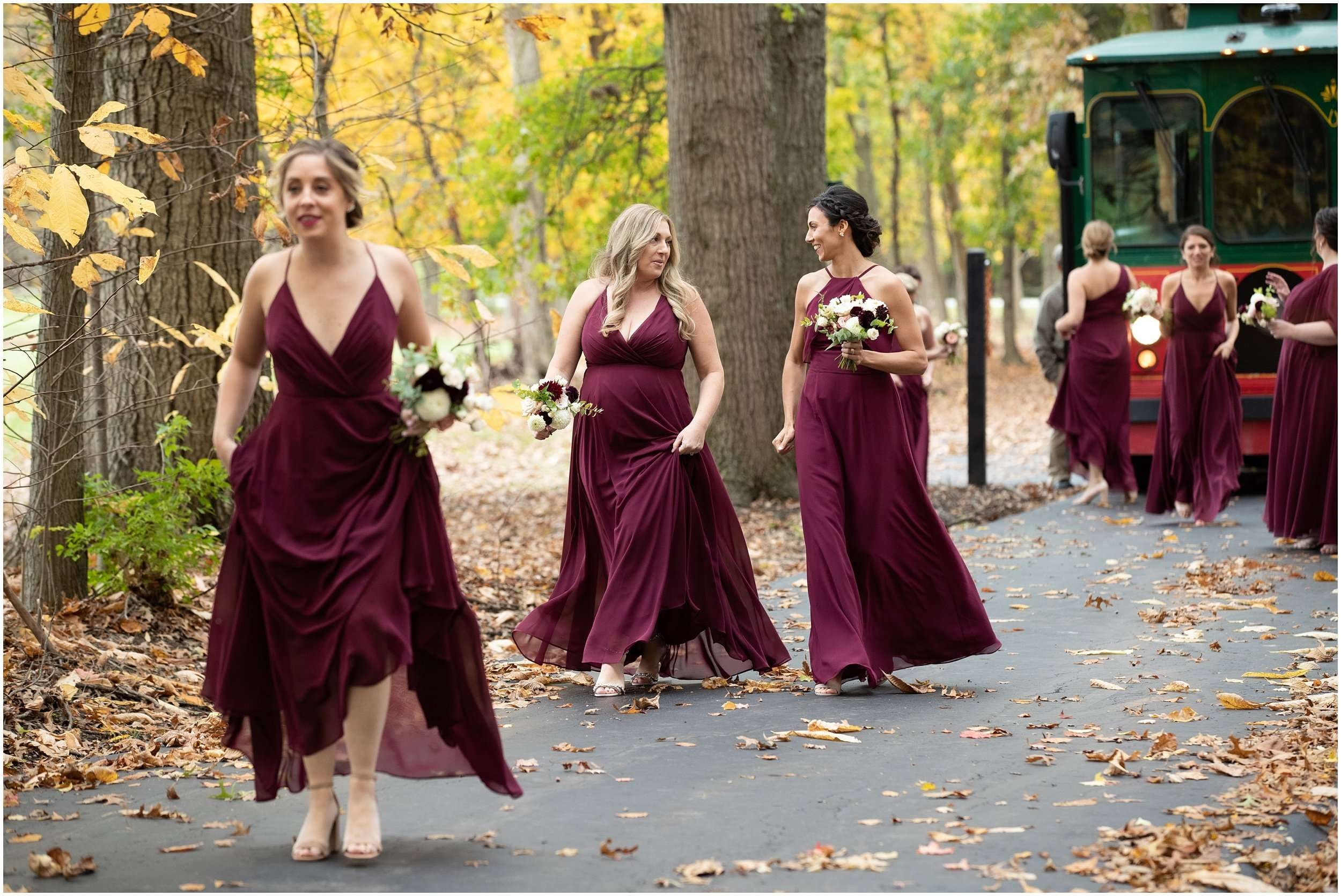 a group of woman wearing long burgundy formal dresses are walking down a long wooded driveway in the fall