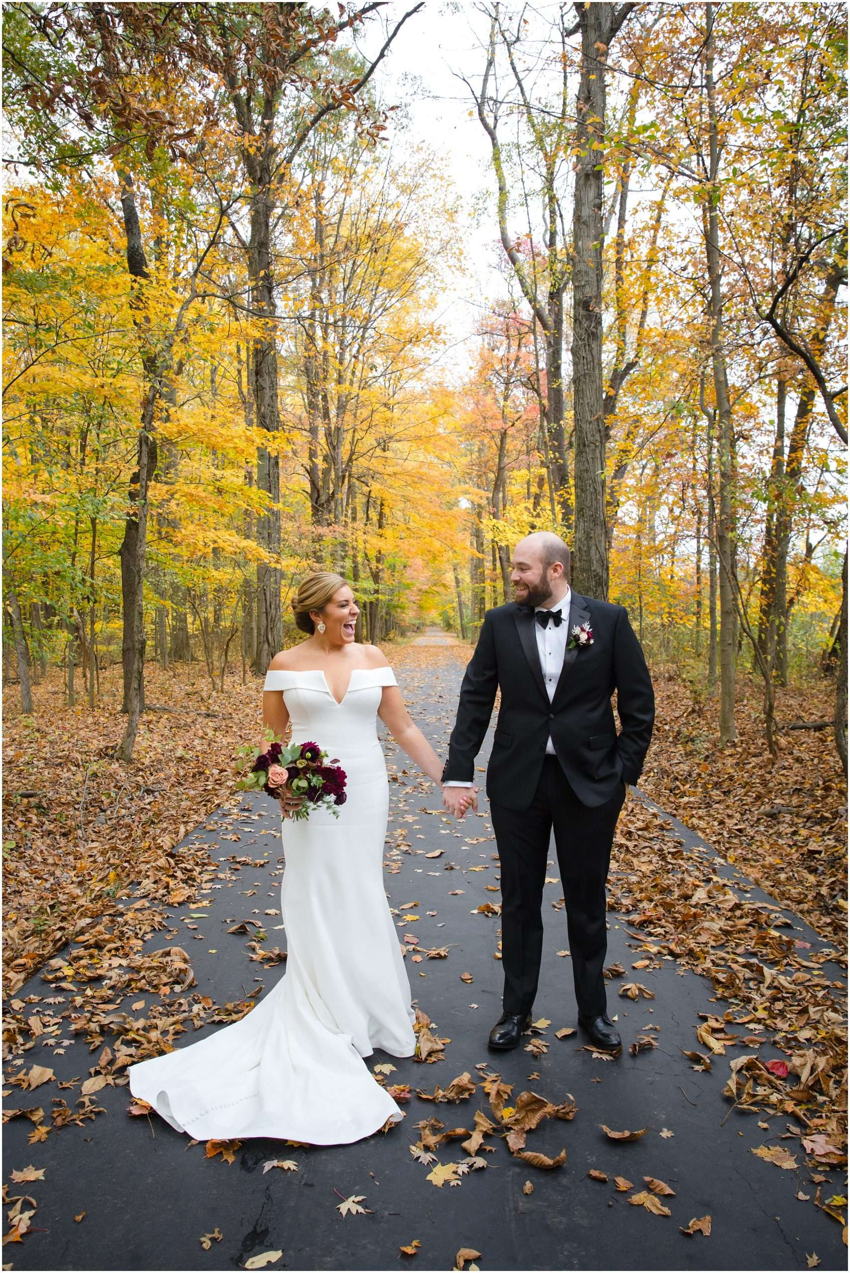 a caucasian bride and groom are holding hands and laughing in the woods on a colorful fall day