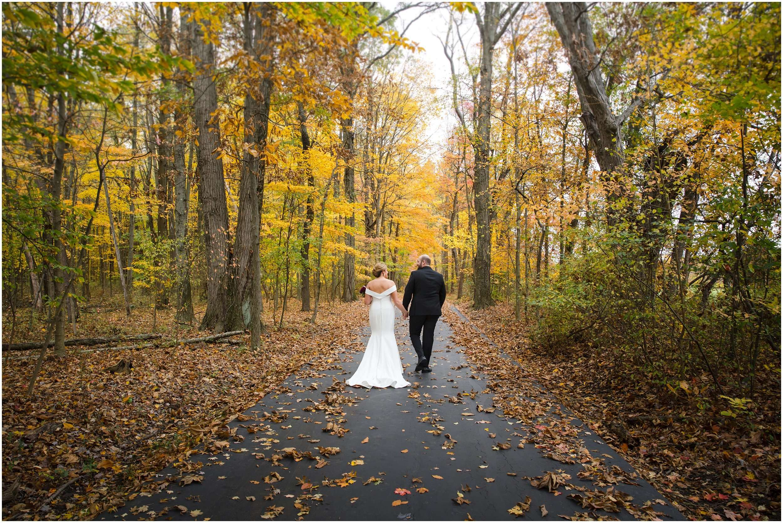 a bride and groom are holding hands and walking down a long paved pathway in the woods among tall orange and yellow trees