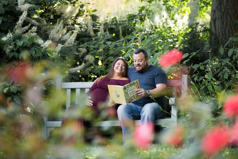 a pregnant woman and man sitting on a bench in a rose garden reading a book to their baby