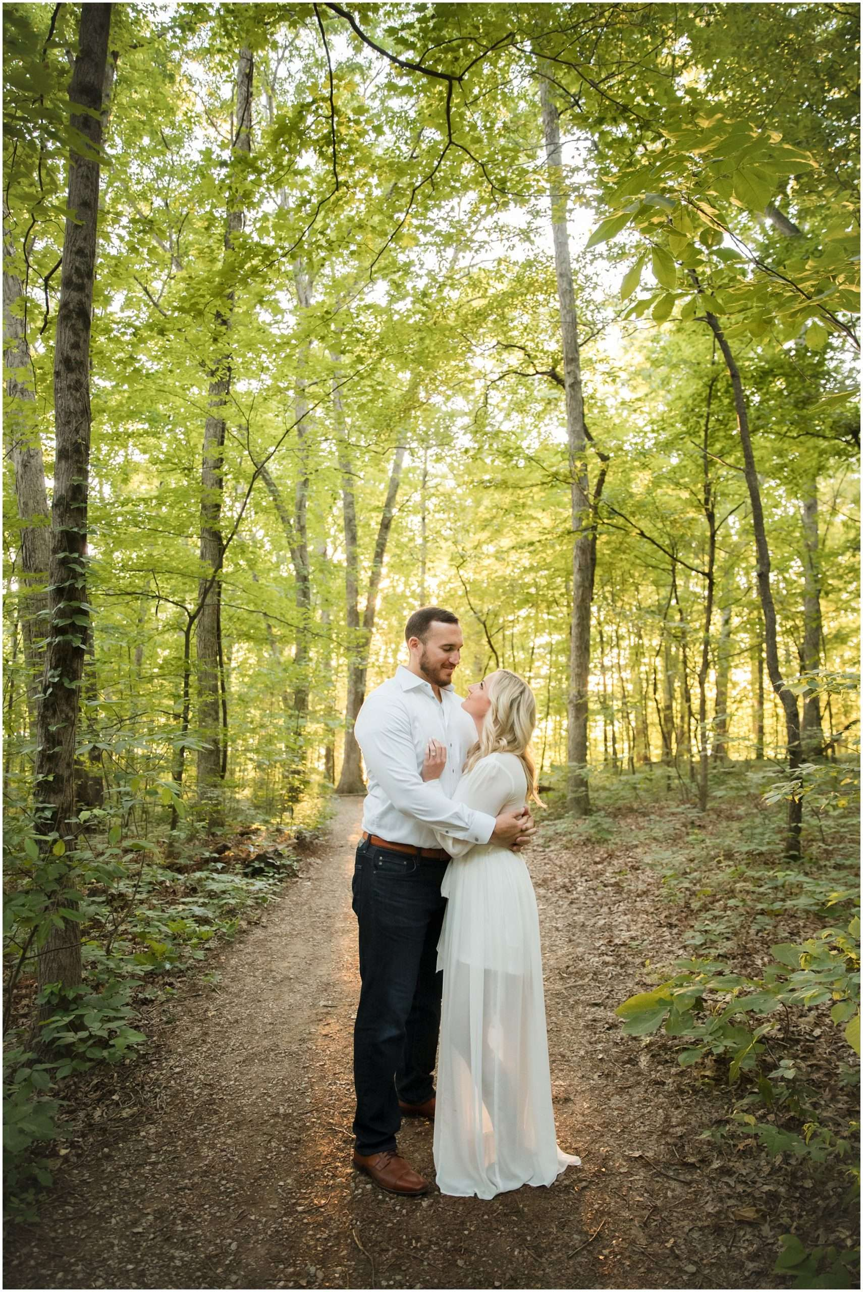 a couple wearing white embraces on a path in the woods with the sun shining through the trees behind them