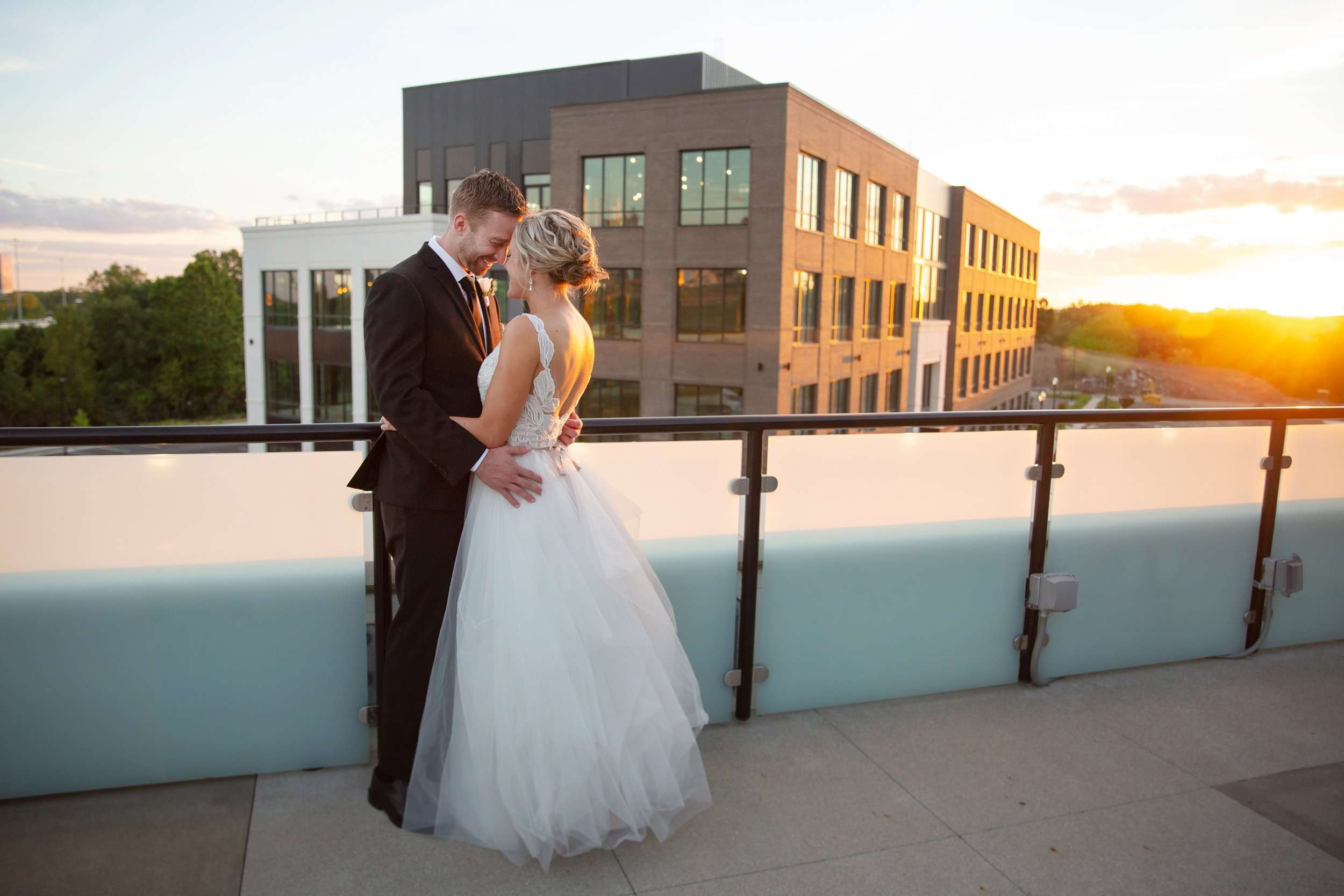 A bride and groom are smiling and holding each other close. The warm glow of the sun setting shines behind them.