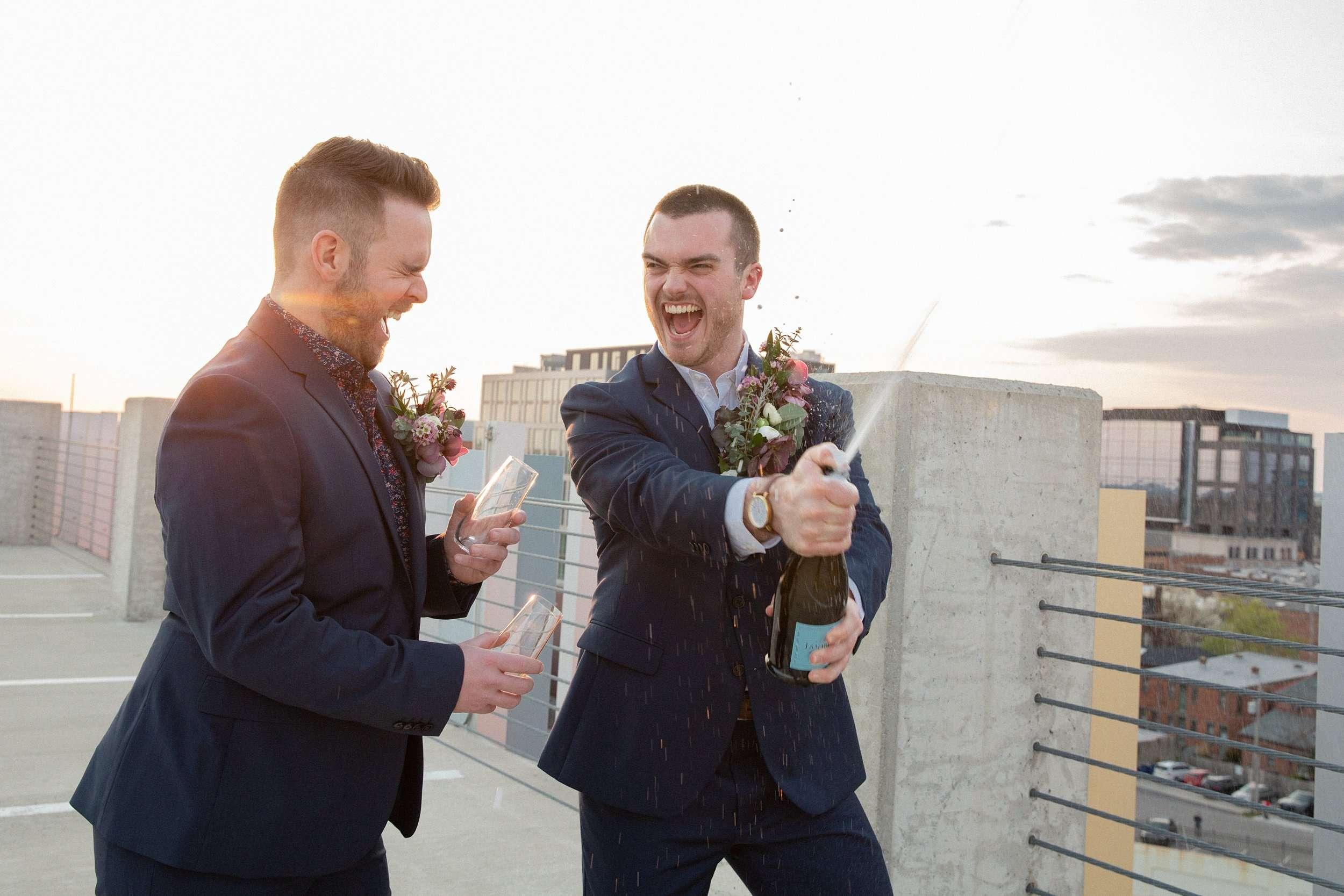 two gay men wearing navy blue suits are laughing while spraying champagne together at sunset in a city setting