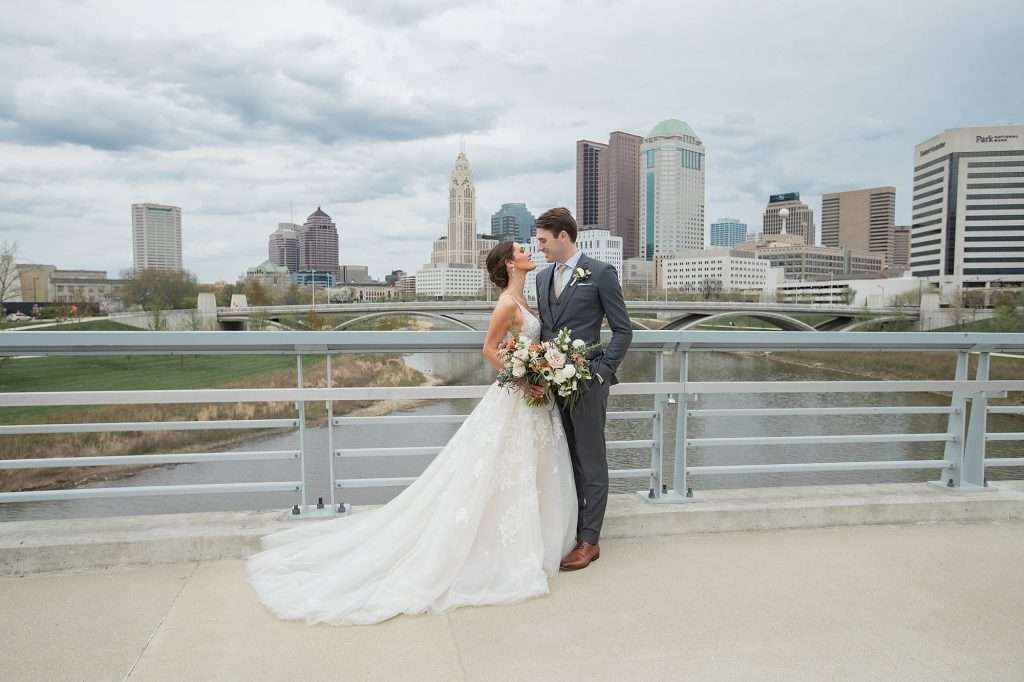 a bride and groom pose together on a bridge overlooking Downtown Columbus Ohio