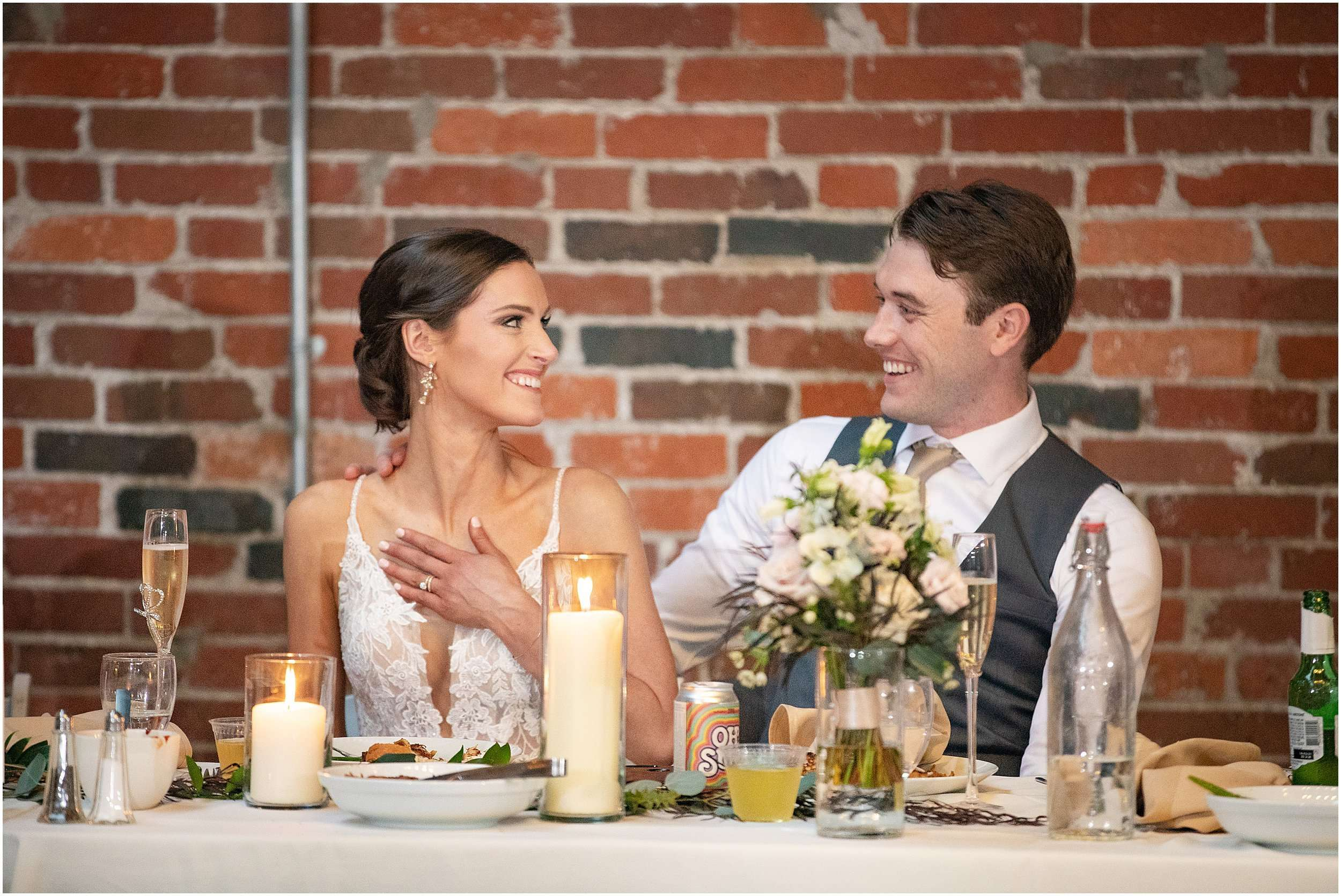 a newly married couple sits at a table full of flowers and candles in front of a brick wall and laughs